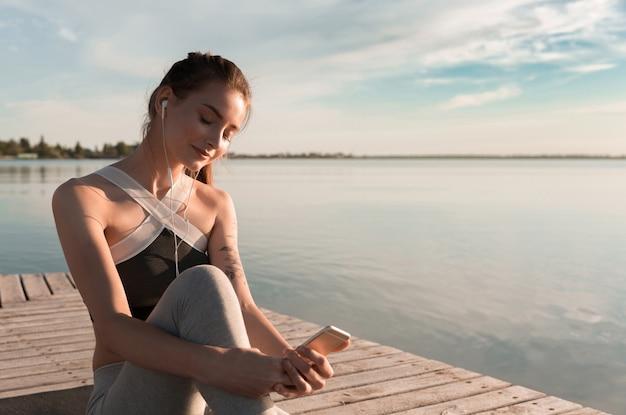 Senhora jovem esportes na praia ouvindo música com fones de ouvido. Foto gratuita