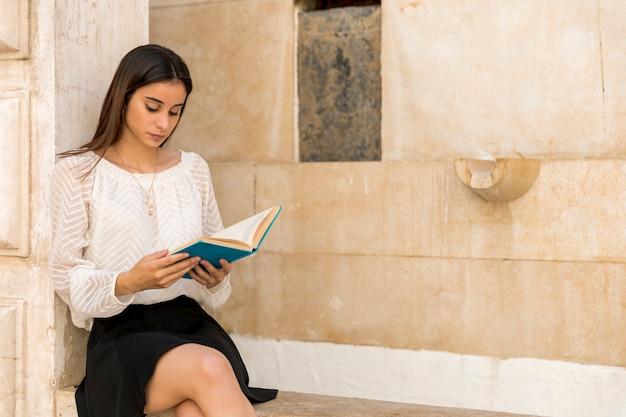 Senhora jovem, sentando, e, livro leitura, perto, edifício pedra Foto gratuita