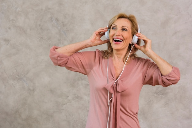 Senhora loira sorridente, ouvindo música no conjunto de fones de ouvido Foto gratuita