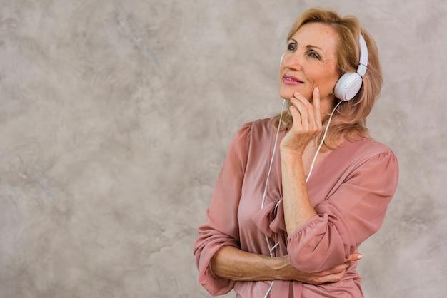 Senhora loira sorridente, ouvindo música no fone de ouvido com espaço de cópia Foto gratuita