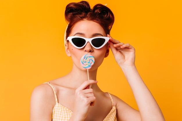 Senhora maravilhosa de óculos de sol, lambendo rebuçados. vista frontal da garota pin-up com pirulito isolado no espaço amarelo. Foto gratuita