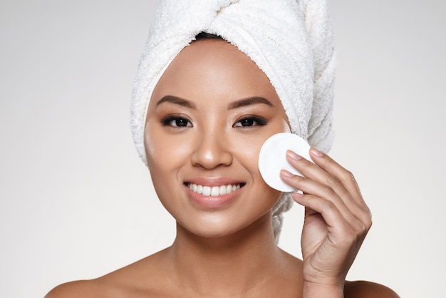 Senhora muito alegre com toalha na cabeça, limpando o rosto Foto gratuita
