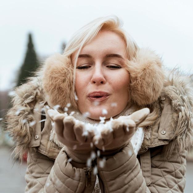 Senhora no inverno soprando na neve Foto gratuita