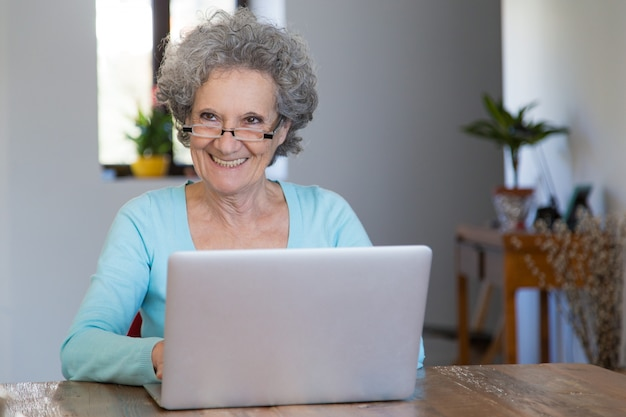 Senhora senior alegre usando serviços on-line Foto gratuita
