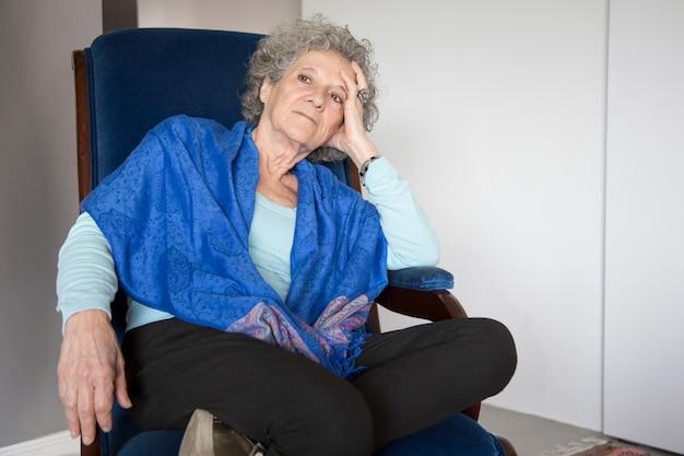 Senhora sênior pensativa sentado na cadeira de balanço e olhando para longe Foto gratuita