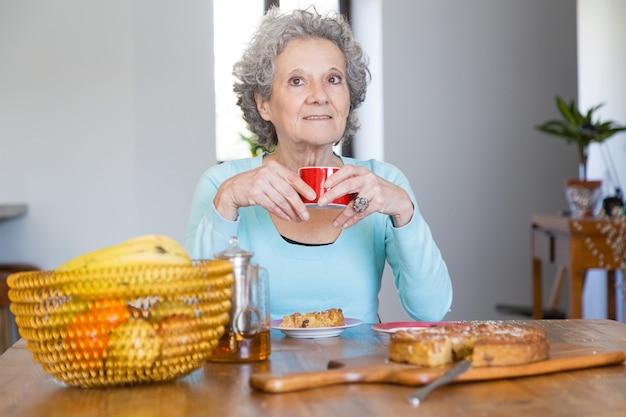 Senhora senior positiva, desfrutando de torta saborosa Foto gratuita