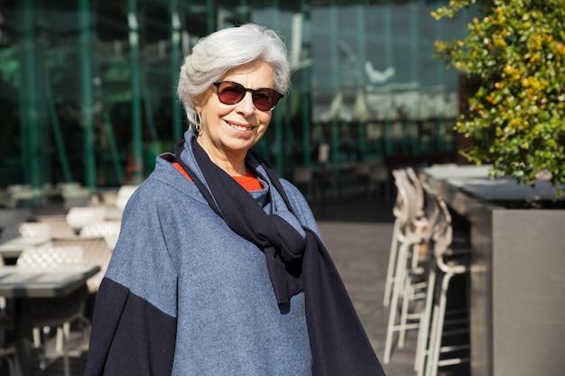 Senhora sênior positiva posando contra café ao ar livre Foto gratuita