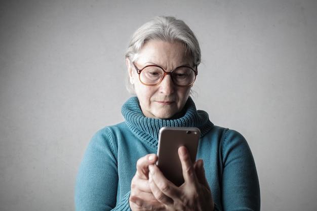 Senhora sênior usando um smartphone Foto Premium