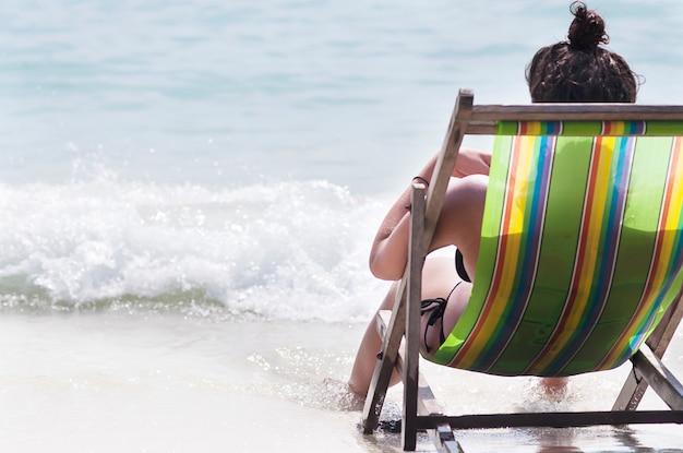 Senhora sentada e lendo na praia relaxar banco na bela praia de areia branca Foto gratuita