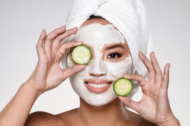 Senhora sorridente atraente com scrab no rosto segurando fatias de pepino Foto gratuita