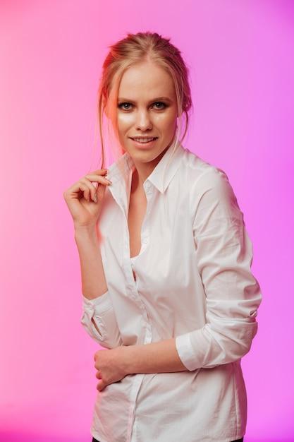 Senhora vestida com camisa branca posando sobre parede rosa. Foto gratuita