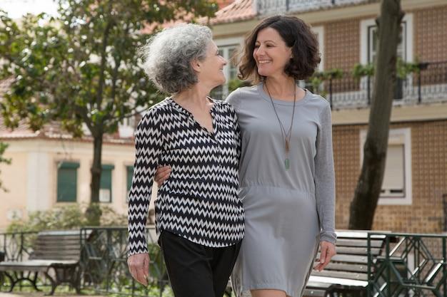 Senhoras alegres jovens e seniores caminhando ao ar livre Foto gratuita