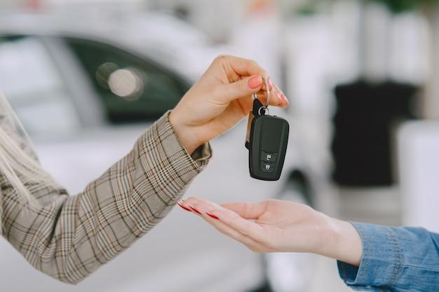 Senhoras em um salão de automóveis. mulher comprando o carro. mulher elegante com um vestido azul. o gerente dá as chaves ao cliente. Foto gratuita