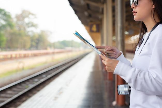 Senhoras felizes que viajam no conceito de turismo de estação de trem Foto gratuita