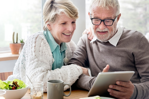 Senior adulto segurando o conceito de leitura tablet Foto Premium