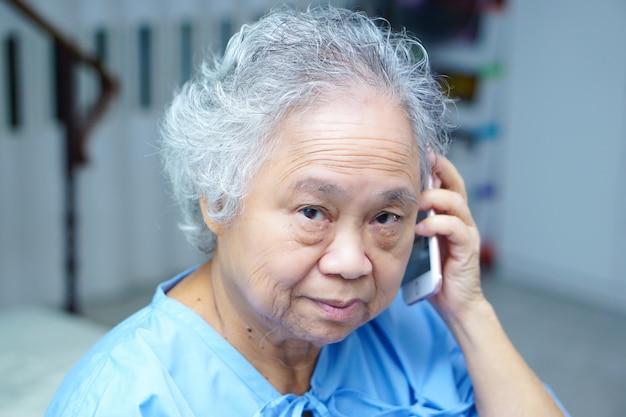 Sênior asiático ou paciente idoso da mulher da senhora idosa que fala pelo telefone celular. Foto Premium