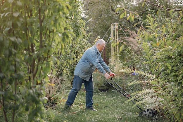 Senior corta a grama no quintal com um cortador de grama Foto gratuita
