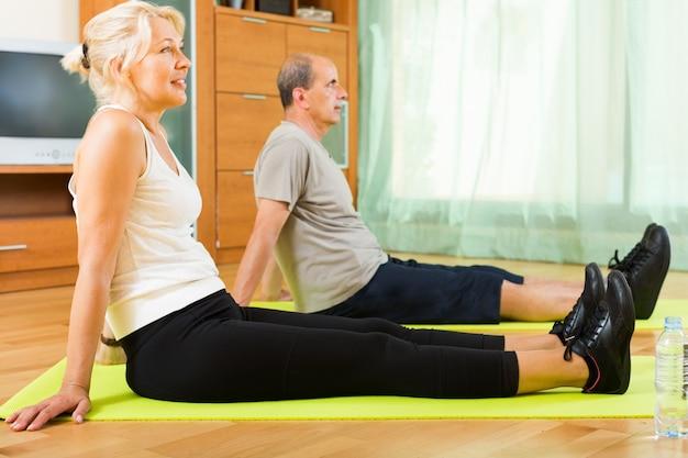 Senior couple fazendo exercícios indoor Foto gratuita