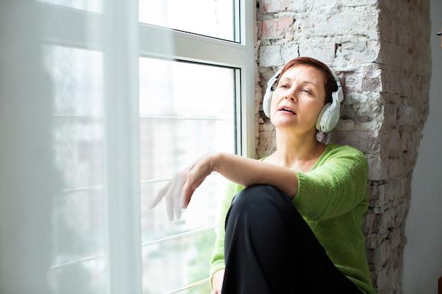 Senior de baixo ângulo, sentado ao lado da janela Foto gratuita