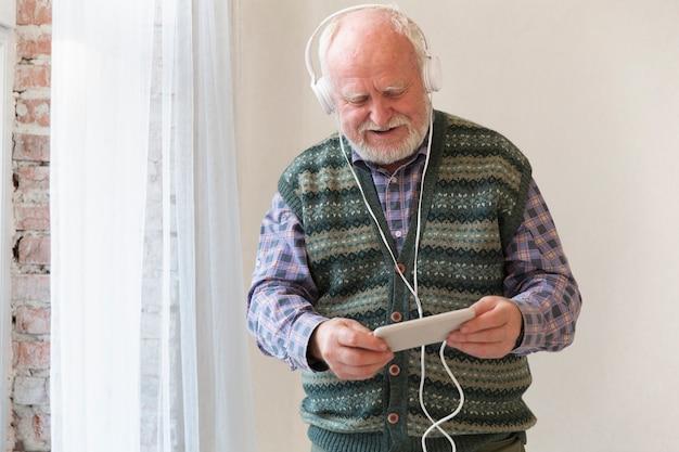 Sênior de baixo ângulo tocando música no telefone Foto gratuita