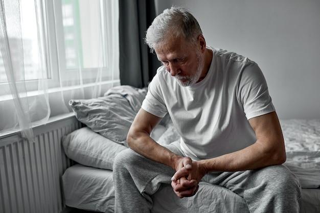 Sênior deprimido sentado pensativo olhando para baixo, homem melancólico sozinho em casa Foto Premium