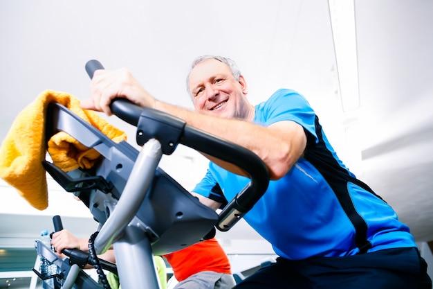Senior fazendo esporte na bicicleta de spinning no ginásio Foto Premium