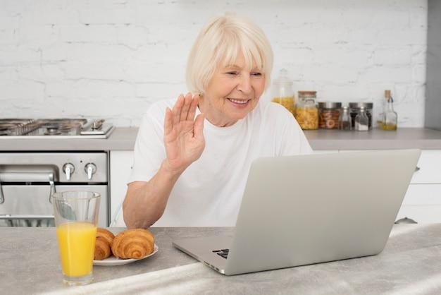 Sênior feliz com um laptop e um copo com suco Foto gratuita