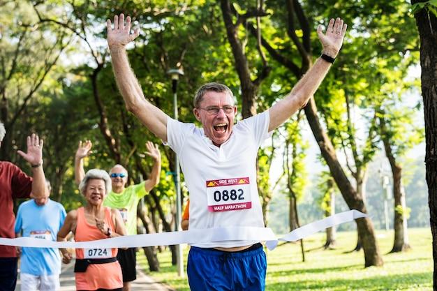 Senior feliz correndo pela linha de chegada Foto gratuita
