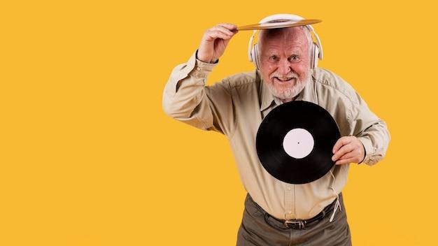 Senior feliz tocando com discos de música Foto gratuita
