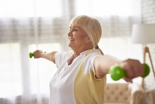 Senior lady dumbbells exercise workout em casa. Foto Premium