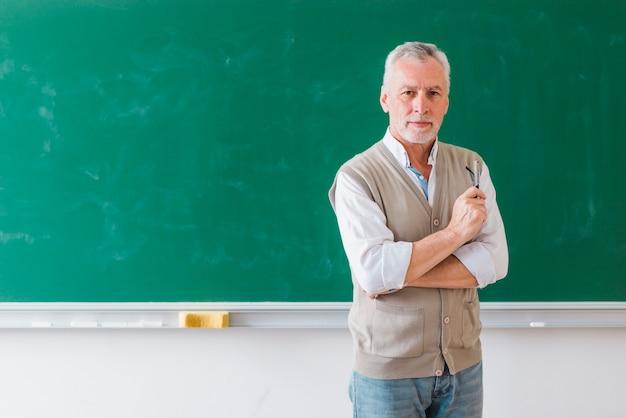 Sênior, macho, professor, ficar, contra, verde, chalkboard Foto gratuita