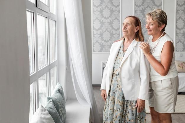 Senior mãe e filha olhando pela janela em casa Foto gratuita