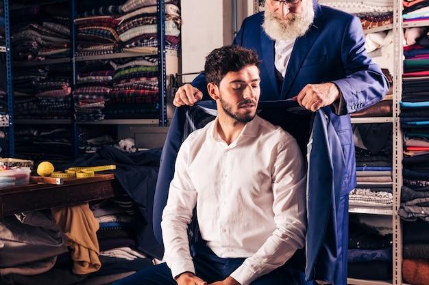 Senior masculino estilista tentando casaco sobre seu cliente na loja Foto gratuita