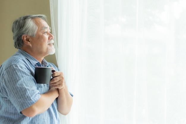 Senior masculino se sentir feliz bebendo café da manhã, aproveitando o tempo em sua casa fundo interior Foto Premium
