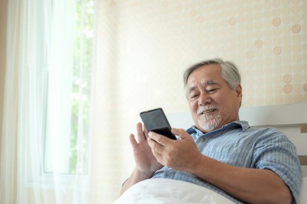 Senior masculino usando um smartphone, sorrindo sentir-se feliz na cama em casa - conceito sênior de estilo de vida Foto Premium
