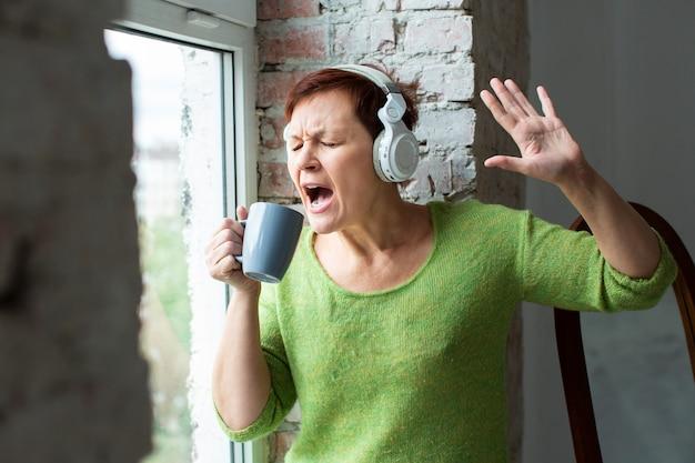 Sênior mulher cantando na xícara de café Foto gratuita