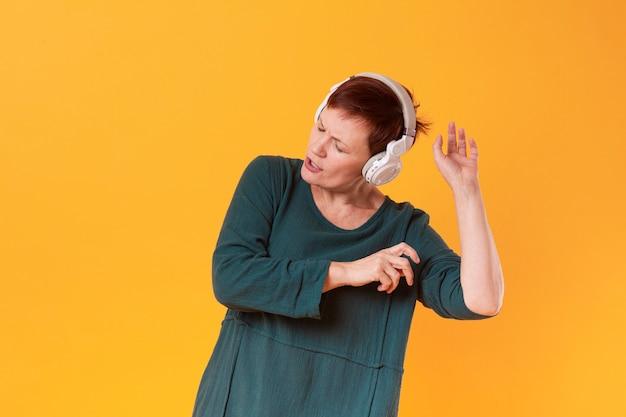 Sênior mulher dançando e ouvindo música Foto gratuita