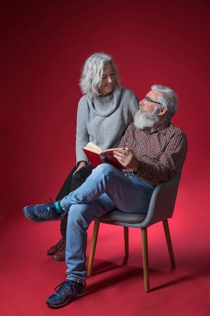 Sênior mulher sentada com o marido sentado na cadeira, segurando o livro na mão contra o fundo vermelho Foto gratuita