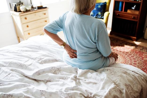 Sênior mulher sentada na cama com dor Foto Premium