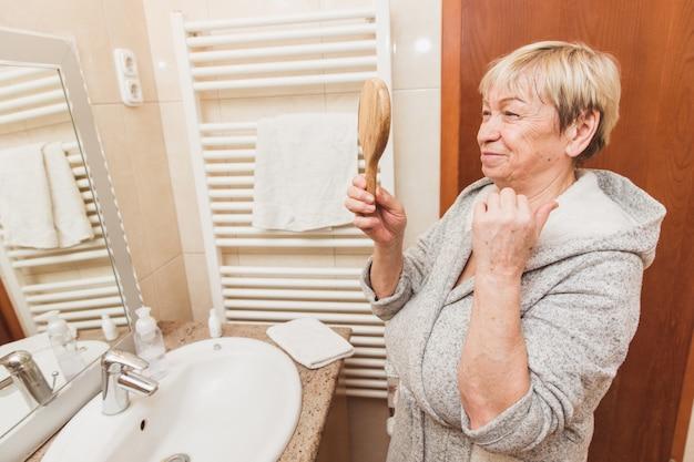 Sênior mulher tocando a pele do rosto macio e olhando no espelho de mão em casa Foto Premium