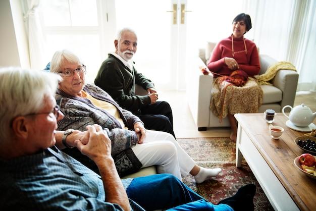 Senior pessoas sentadas juntas em uma sala de estar Foto Premium