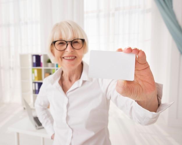 Senior, segurando um cartão de visita com espaço de cópia Foto gratuita