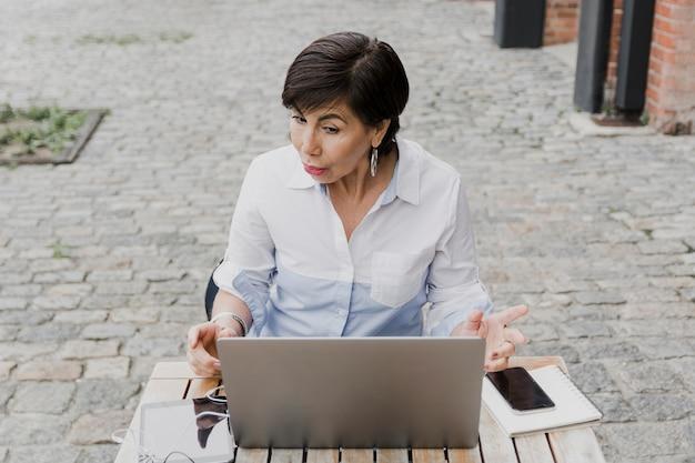 Senior sentado ao ar livre com o laptop tiro médio Foto gratuita