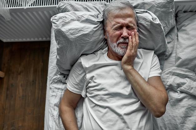 Sênior solitária triste deitada na cama em um hospital, o conceito de hospitalização. sofrendo de doenças, dentes doloridos, choro de dor Foto Premium