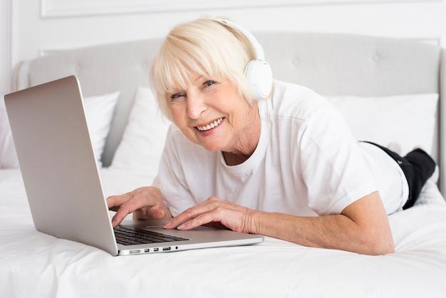 Sênior sorridente com fones de ouvido e laptop Foto gratuita