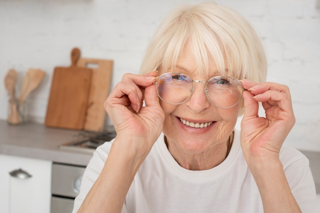 Sênior sorridente segurando um óculos Foto gratuita
