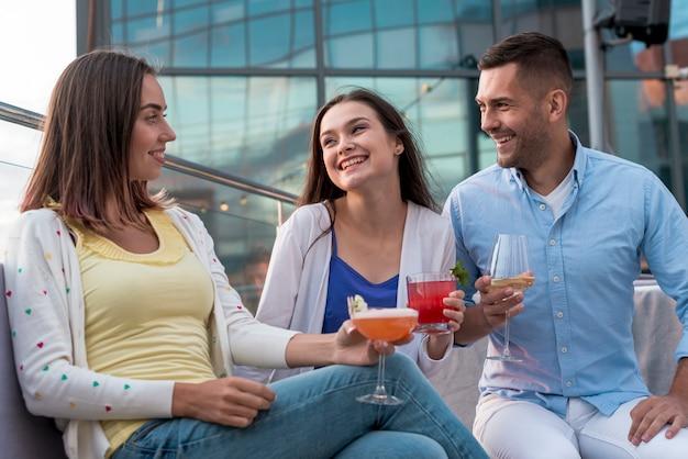 Sentado amigos com bebidas em uma festa Foto gratuita