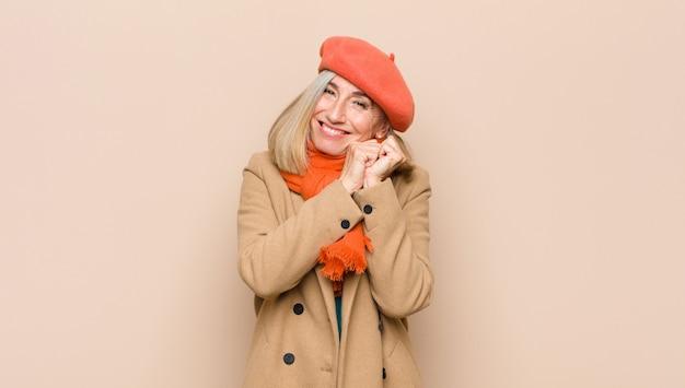 Sentindo-se apaixonado e bonito, adorável e feliz, sorrindo romanticamente com as mãos ao lado do rosto Foto Premium