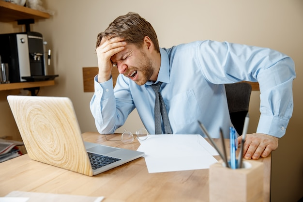 Sentindo-se doente e cansado. homem jovem doente infeliz triste frustrado massageando sua cabeça enquanto está sentado em seu local de trabalho no escritório. Foto gratuita