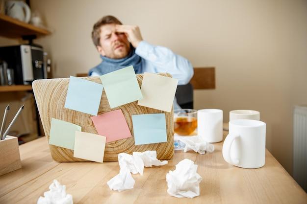 Sentindo-se doente e cansado. jovem frustrado massageando a cabeça enquanto está sentado em seu local de trabalho Foto gratuita